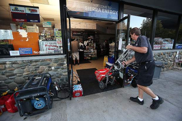 Delivery workers cart in supplies to this Sierra Express gas station in Penn Valley with the help of generators and light stands.