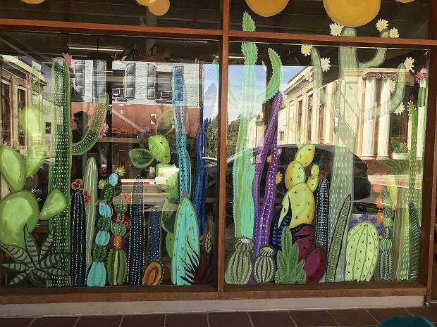 Downtown cactus themed painted storefront with Bank Building reflected in Grass Valley.