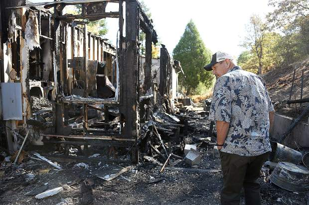 Rough and Ready's Rick Toles walks around the charred skeletal remains of his Lost Trail Way home.