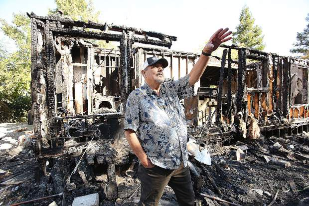 Rough and Ready's Rick Toles indicates where the fire from his home began to travel while he fought the flames with a garden hose Aug. 30 after a propane tank explosion.