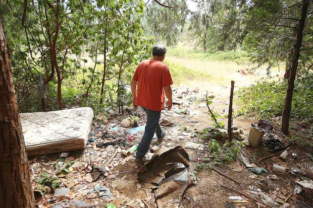 Dick Law, a broker for Paul Law Realty, walks through a pile of trash left from a homeless encampment near the Glenbrook Basin last week. Law plans to schedule a cleanup of the property.