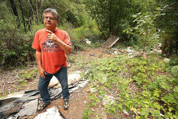 Dick Law, a broker for Paul Law Realty, shows the entry and egress used for the large homeless encampment that once existed at this location off of Brunswick Road. He is now advocating for a cleanup of the private property.