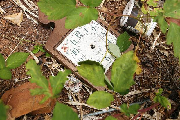 A broken clock sits among the piles of trash left at the property bordering the nearby Hilbers Homes' Timberwoods Estates housing development.