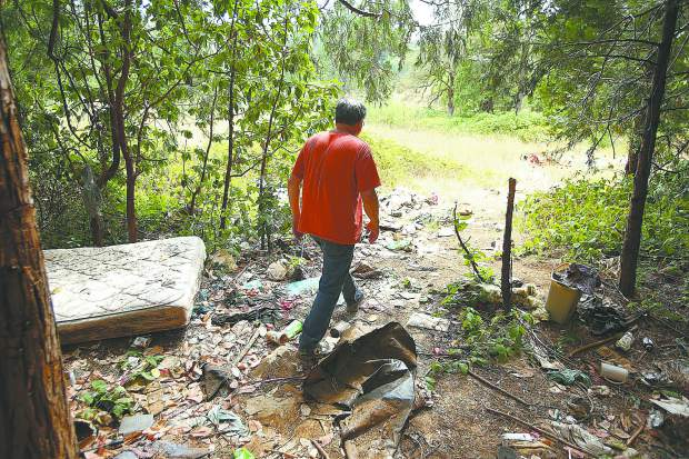 Dick Law, a broker for Paul Law Realty, walks through a pile of trash left from a homeless encampment near the Brunswick Basin last week. Law plans to schedule a cleanup of the property.