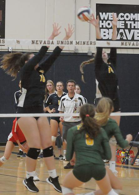 Nevada Union's Emerson Dunbar (14) and Ashlyn Franssen (18) go up for the block during a contest with Placer Monday at Albert Ali Gymnasium.