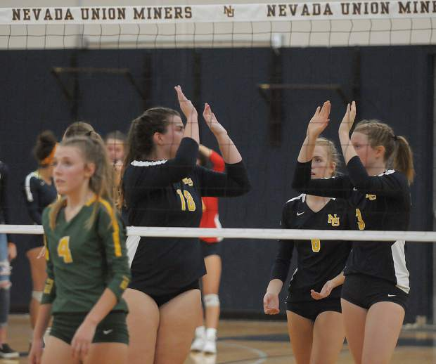 Nevada Union players Ashlyn Franssen (18) and Faith Menary (3) celebrate a point during the Lady Miners' straight set win over Placer Monday at Albert Ali Gymnasium.