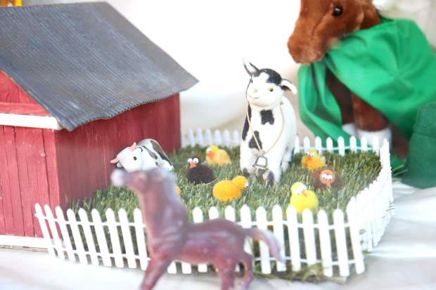 A detail of the Misty Mountain 4-H window display shows happy cows and chickens outside of a red barn.