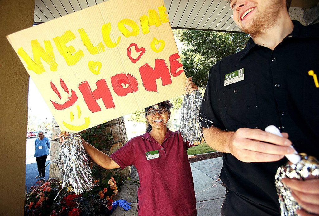 Atria Grass Valley housekeeper Nina Underwood dances and shakes a sign welcoming the Atria assisted living center residents home Wednesday morning.