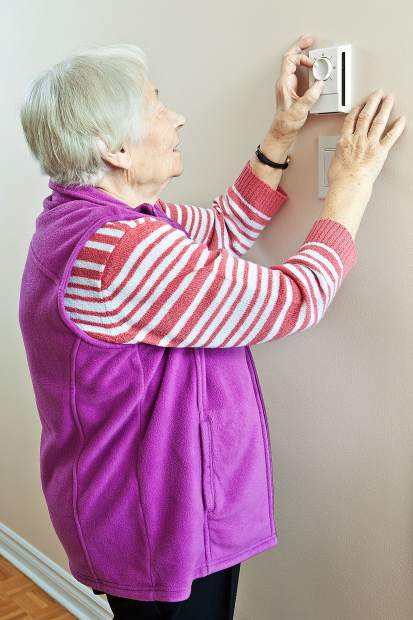 Senior woman saving energy by dressing warm and adjusting her thermostat