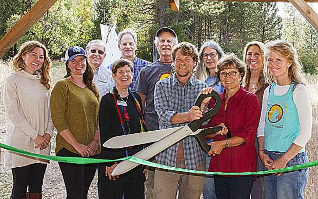Rick Berry, Founder and Director of 4 Elements Earth Education, surrounded by Board of Directors for the Bear Yuba Land Trust and 4EEE, along with Nevada City Mayor Renette Senum, cuts the ribbon signifying the transfer of ownership of Burton Homestead from the land trust to 4EEE.