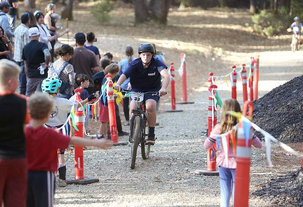An intermediate racer crosses the finish line to much support from the crowd.