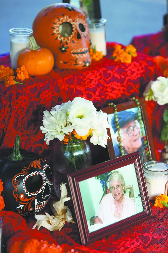 Photos of loved ones accompany painted skulls on on altar set up for the Dia De Los Muertos celebration at Bell Hill Academy.