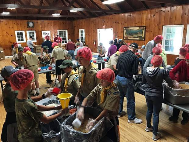 Trinity Parishioners and Scouts pack meals for food-insecure children.