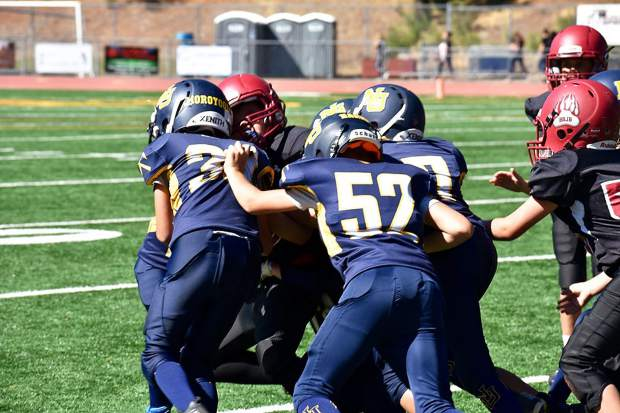 A host of Jr. Miners tackle a Jr. Bruins ball carrier during the 10U game Saturday at Hooper Stadium.
