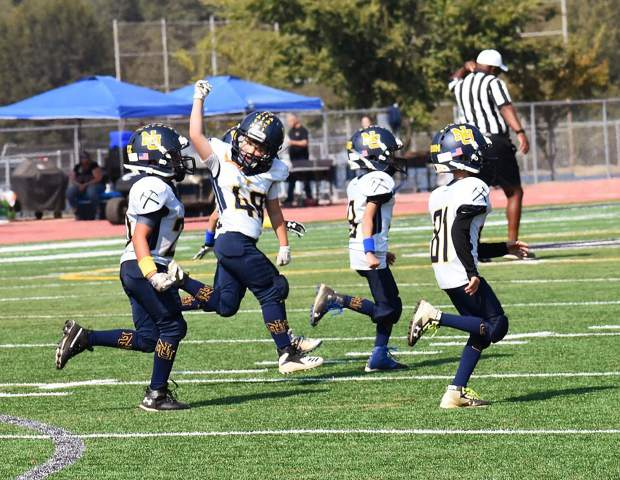 The Nevada Union 8U Jr. Miners run off the field after a 12-6 double overtime victory over Casa Roble Saturday.
