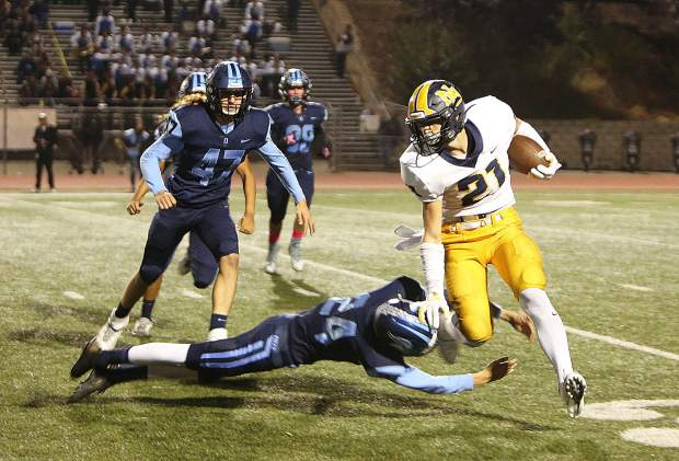 Nevada Union senior running back Jaxon Horne (21) ditches defenders as he picks up yards for the Miners during their 34-21 point loss to the Oakmont Vikings.