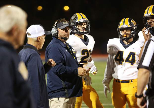 Varsity Miners head coach Brad Sparks talks to his players on the sideline in between plays Friday against Oakmont.