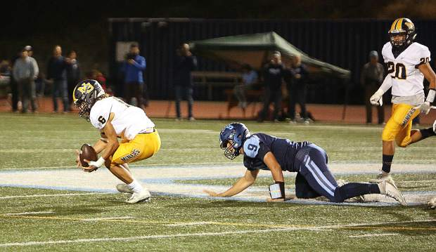Nevada Union's Zach Ehrlich (6) recovers a fumble from Oakmont quarterback Hayden Abbruzzese (9) during Friday's league loss to the Vikings.