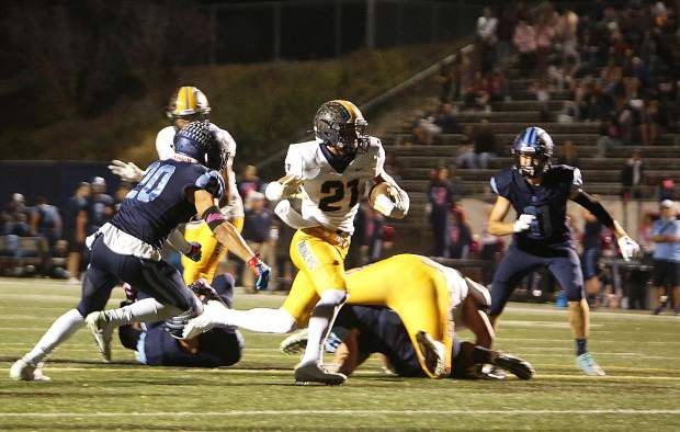Nevada Union running back Jaxon Horne makes his way past Oakmont defenders as eyes the end zone for the Miners.