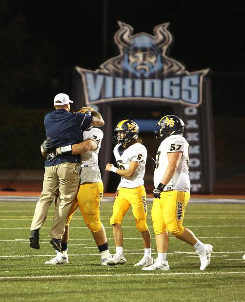 Nevada Union defensive tackle Isaiah Carter (74) is congratulated after picking an interception thrown by Oakmont quarterback Hayden Abbruzzese during the Miners' 34-21 loss to the Vikings.