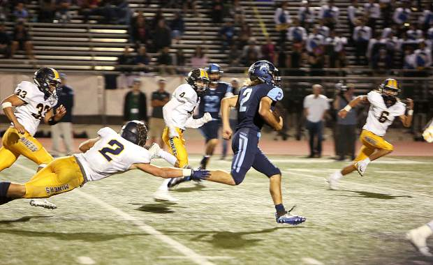 Oakmont running back Kane Rosko (2) evades a slew of Miners during Friday's league matchup.