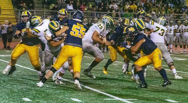 Placer's Hans Grassmann (25) runs the ball during a game against Nevada Union Friday night at Hooper Stadium.