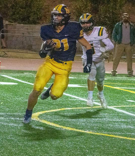 Nevada Union's Jaxon Horne looks for running room during a game against Placer Friday night at Hooper Stadium.