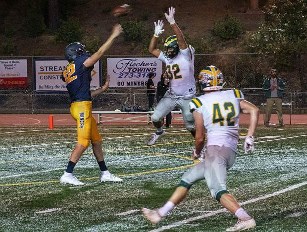 Nevada Union's J.T. Conway gets the ball away ahead of the rush during a game against Placer Friday night at Hooper Stadium.