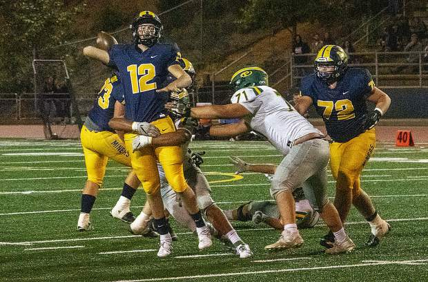 Nevada Union's J.T. Conway gets the ball away as Placer defenders close in on him during a game Friday night at Hooper Stadium.