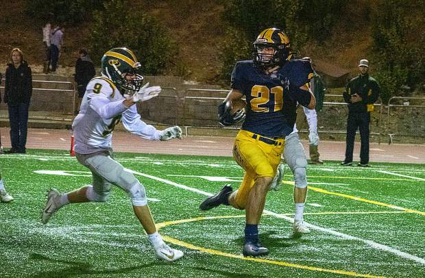 Nevada Union's Jaxon Horne (21) looks for running room during a game against Placer Friday night at Hooper Stadium