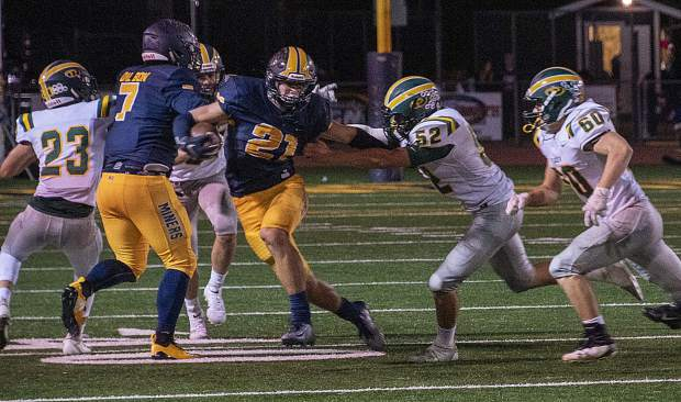 Nevada Union's Jaxon Horne (21) looks for running room during a game against Placer Friday night at Hooper Stadium.