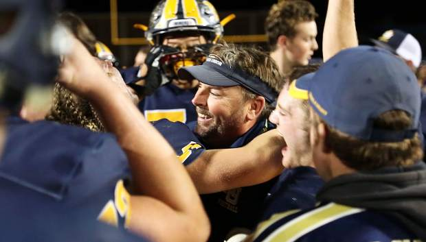Nevada Union varsity football head coach Brad Sparks is embraced by his team following The Miners' win over league opponent Ponderosa marking the first league win for NU since 2012.