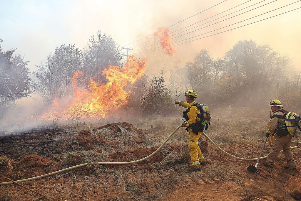 Firefighters work the active flames of an approximately 15-acre vegetation fire which started near the intersection of Dorsey Drive and Sutton Way in Grass Valley Sunday about 1:30 p.m.