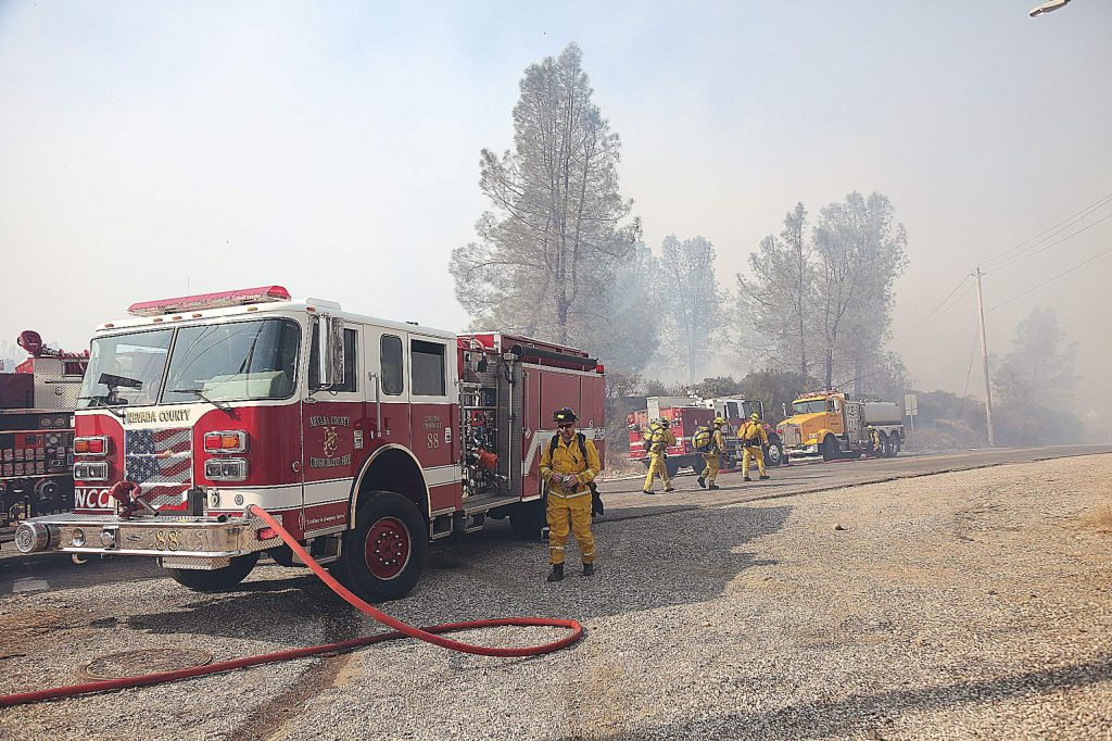 Firefighters man their engines ensuring that water is flowing to the firefighters on the front lines of the Dorsey Fire Sunday in Grass Valley.