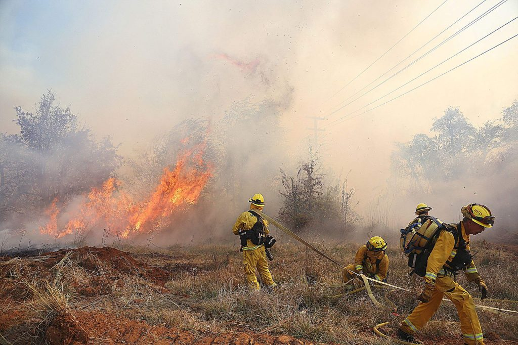 Firefighters keep an eye on flare ups and spot fires of the Dorsey Incident Sunday afternoon near Dorsey Drive and Sutton Way in Grass Valley.