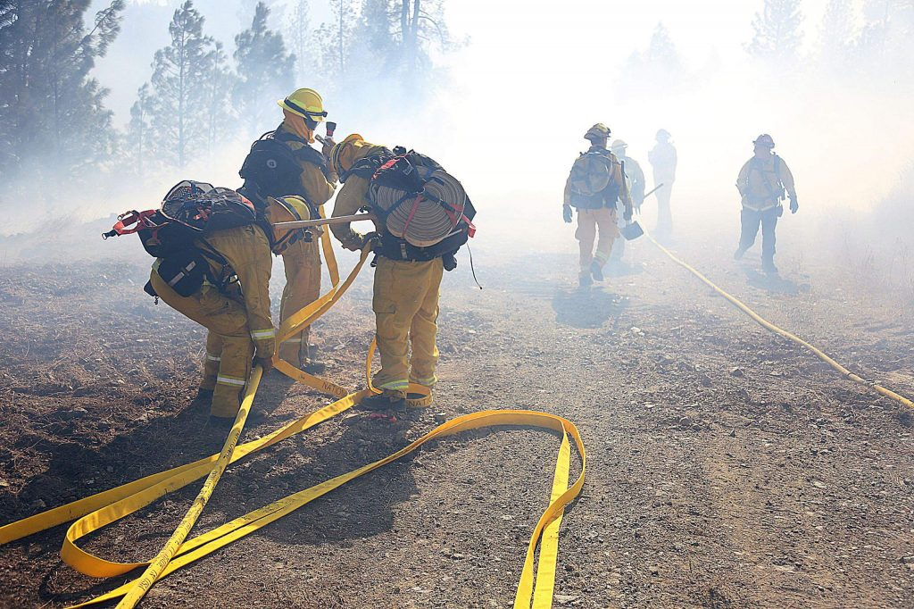 Firefighters connect hose for a hose lay before entering the Dorsey Incident Sunday in Grass Valley.