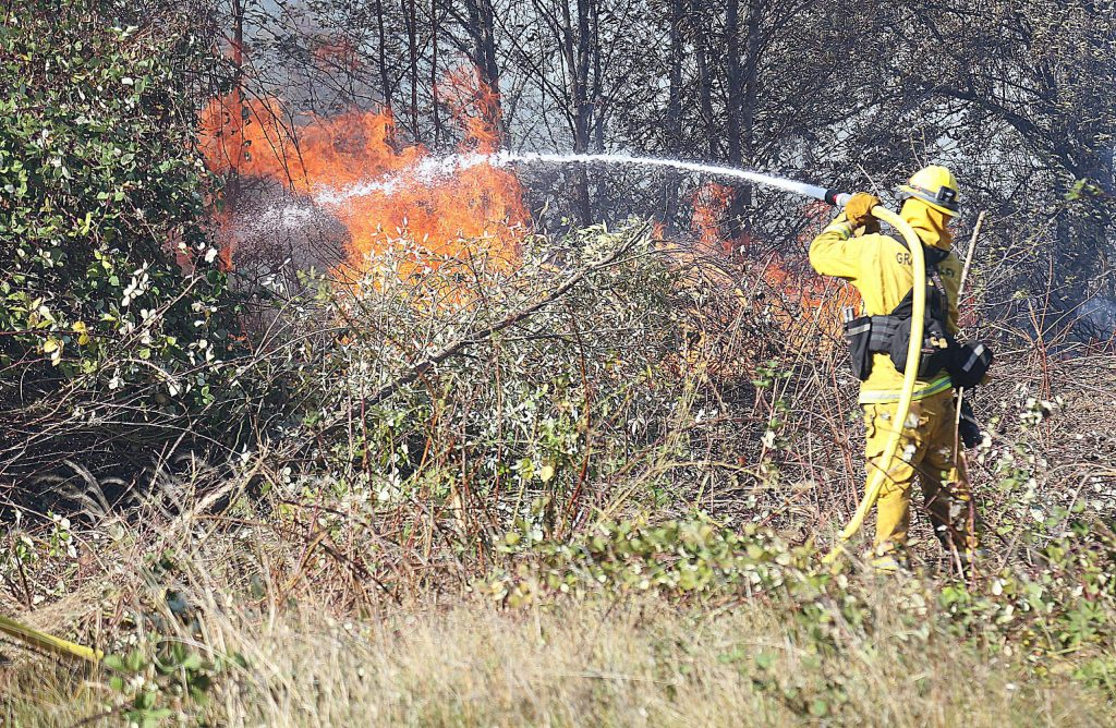 A firefighter gets water on a spot fire that flared up along the fire lines of the Dorsey Fire Sunday near the intersection of Dorsey and Sutton Way in Grass Valley.