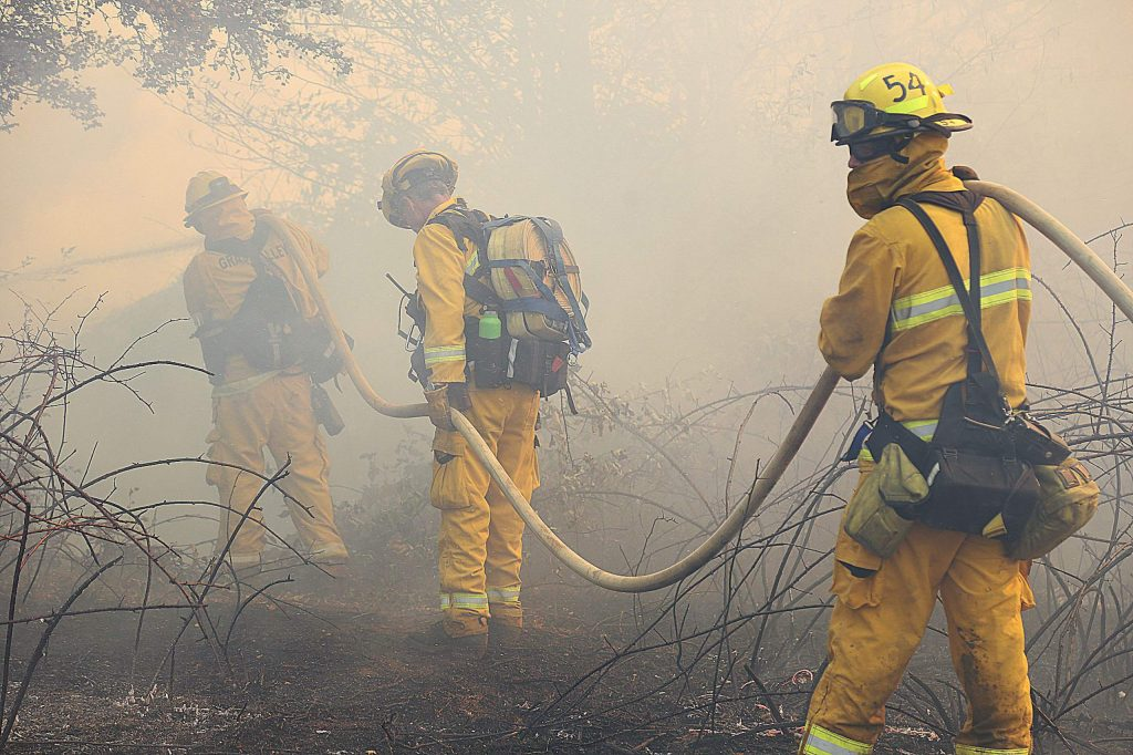 Firefighters work through the smoke of the Dorsey Incident Sunday near Dorsey and Sutton Way in Grass Valley. The fire, which started about 1:30 p.m., was 75 percent contained by 3:45 p.m.