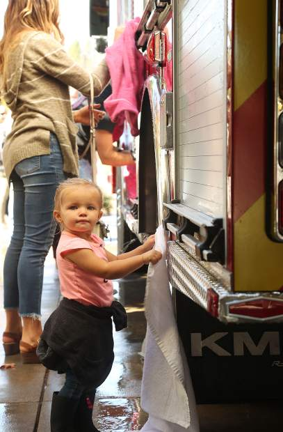 One year old Mikynlie Ramirez helps to dry the new Grass Valley Fire Engine No. 2 after it received its first wash Saturday outside of the bays of station 2.