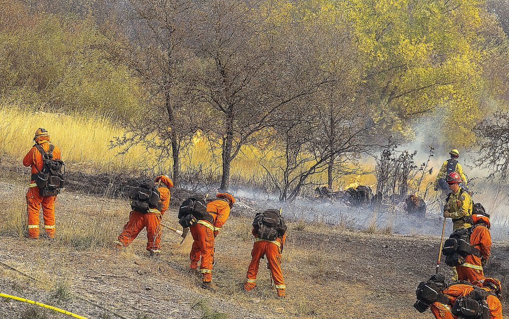 A fire crew from Deadwood Conservation Camp builds a fire line at the vegetation fire that broke out off Sutton Way at Dorsey Drive Sunday afternoon.