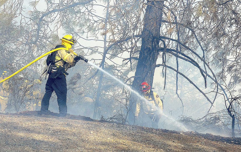 A firefighter puts water on a hot spot at the Sunday fire.