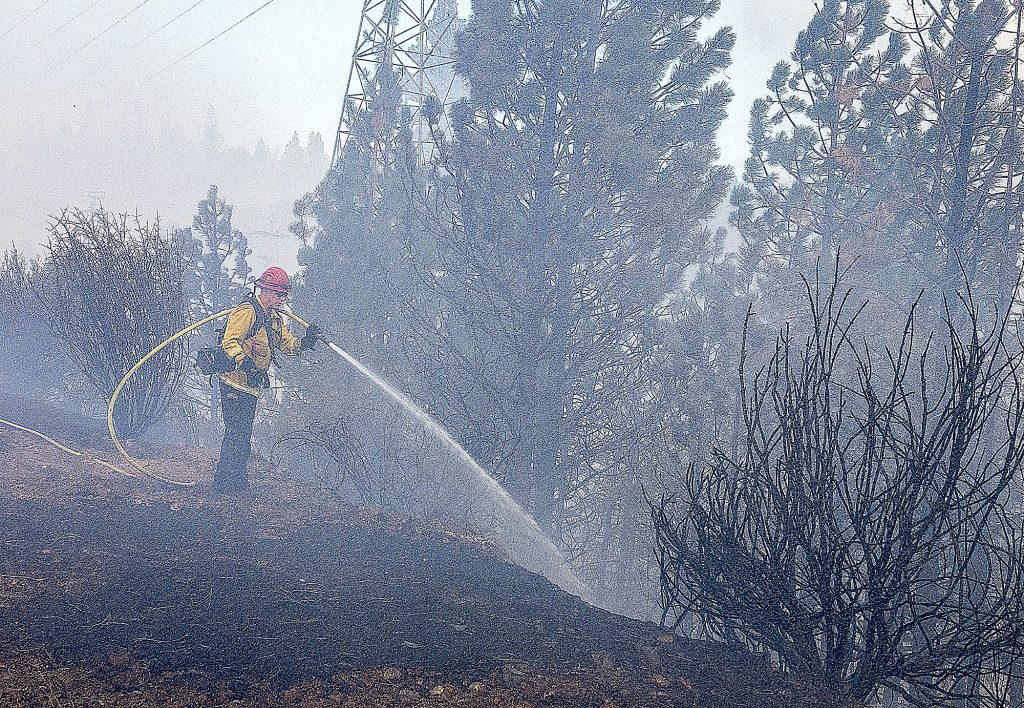 A firefighter sprays water to cool down the vegetation fire that broke out on Sutton Way at Dorsey Drive, Grass Valley, Sunday afternoon.