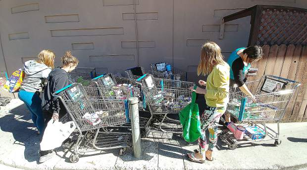 Folks seek to utilize melting ice cream and other discarded perishables from SPD Market in Nevada City. 75 shopping carts full of items were gone within minutes once word spread of the wasting food.