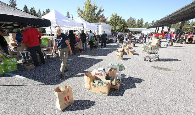 Piles of free groceries stack up as people collect different items given during the Emergency Food Distribution hosted by the Food Bank of Nevada County Thursday morning at the Rood Center.
