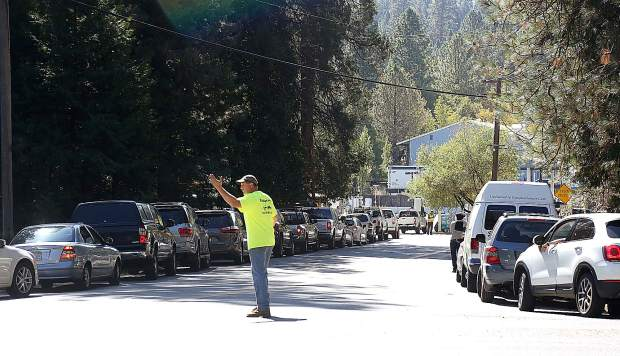A Robinson Enterprises employee works to direct traffic along Ridge Road at Lower Grass Valley Road as folks wait in line for some of the few working gas pumps in the county. Wait lines were upwards of 2.5 hours.