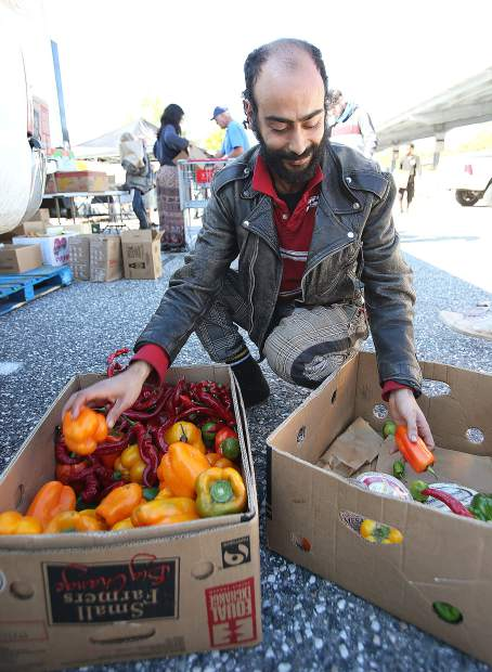 Simo Boughad, currently touring Nevada County from Morocco, grabs fresh vegetables from a box donated from Briar Patch Food Co-Op during Thursday morning's Emergency Food Distribution at the Rood Government Center.