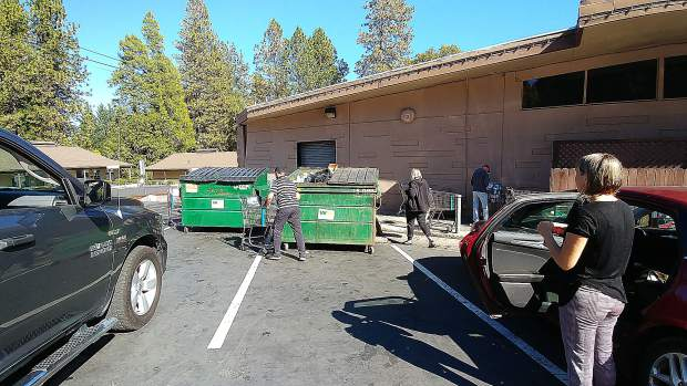 Folks check to see if they can scavenge from shopping carts full of discarded perishables outside of SPD Nevada City Thursday afternoon. 75 carts full of food were gone in minutes.
