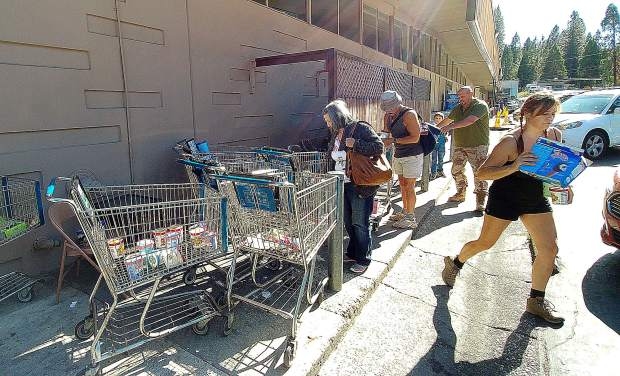 Folks grab ice cream and other perishables discarded from the freezers at SPD Market in Nevada City Thursday morning after discovering 75 shopping carts full of items slated for the dumpster.