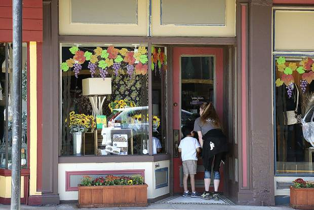 Shoppers peer into the closed storefronts along Mill Street in downtown Grass Valley during the PG&E public safety power shutdown.
