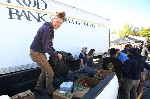 Briar Patch sustainability coordinator and Sierra Harvest procurement specialist Lauren Scott helps to unload a truckload of food donated from Briar Patch Co-Op during Thursday morning's Emergency Food Distribution hosted by the Food Bank of Nevada County at the Rood Government Center.